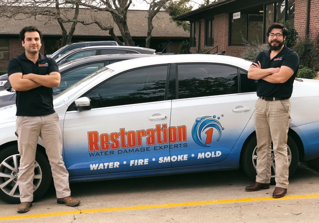 two men stand next to Restoration 1 car image