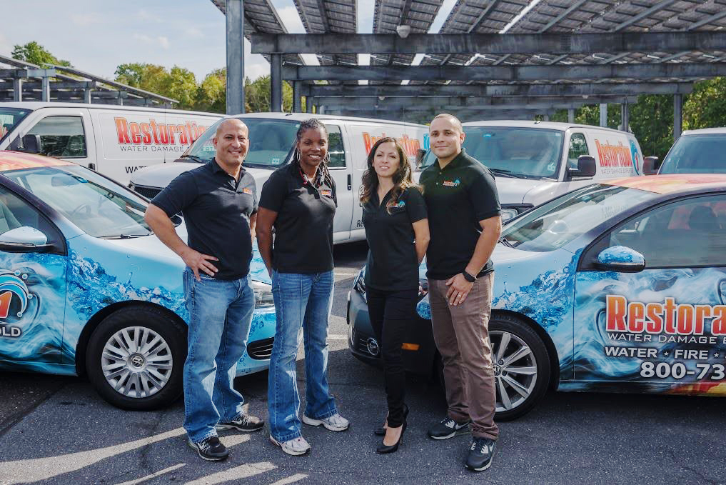 Restoration Franchise owners standing in front of their fleet of restorative vehicles